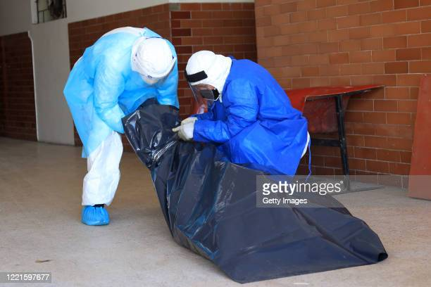 Personnel of Loreto Regional Hospital Felipe Santiago Arriola Iglesias wearing PPE suits wrap the corpse of COVID-19 victim in a plastic bag to take...