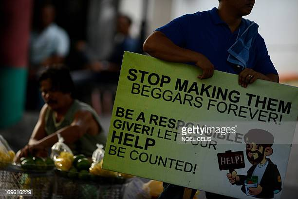 A personnel of Makati Social Welfare Department holds a banner with a message discouraging people on giving alms on beggars at a street in Manila on...
