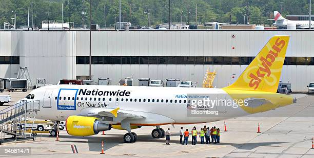 Personnel stand at the rear of a Skybus Airlines Airbus 319 aircraft as it sits on the tarmac at Port Columbus Airport in Columbus Ohio Monday May 21...