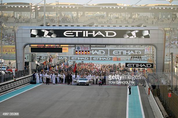 F1 personnel teams and media mill around on the starting grid before the start of the Abu Dhabi Formula One Grand Prix at the Yas Marina circuit on...