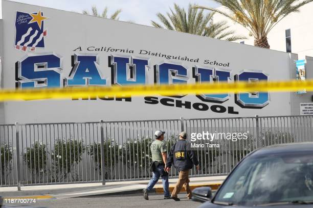 FBI personnel walk at Saugus High School after a shooting at the school left two students dead and three wounded on November 14 2019 in Santa Clarita...