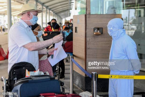A personnel wearing protective gear checks passports of British nationals queueing before checkingin for a special flight to London after the...