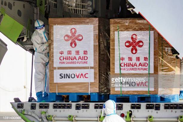 Personnel wearing protective suits handle crates containing Sinovac Biotech COVID-19 vaccines aboard a Chinese Airforce plane upon arriving at Ninoy...