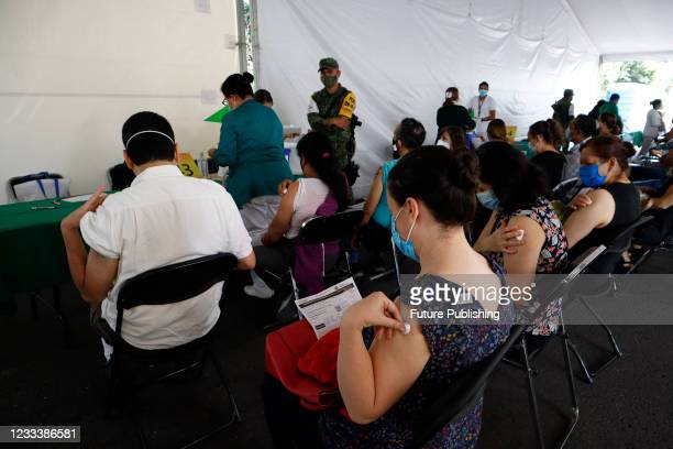 Persons are seen in waiting zone after receive a Pfizer BioNTech dose during mass vaccination campaign for people of 40 to 49 years old to immunize...
