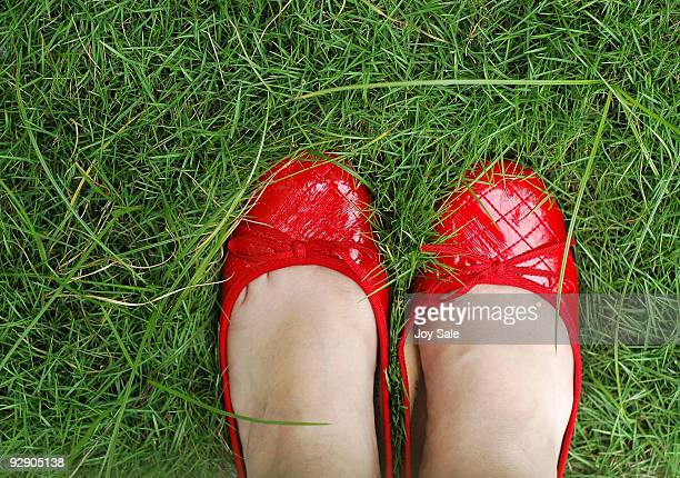 Person's Feet  Wearing Red Shoes on Green Grass