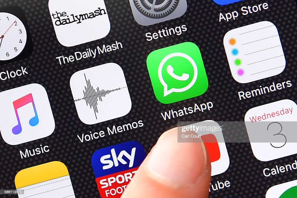 A persons finger is posed next to the Whatsapp app logo on an iPhone on August 3, 2016 in London, England.