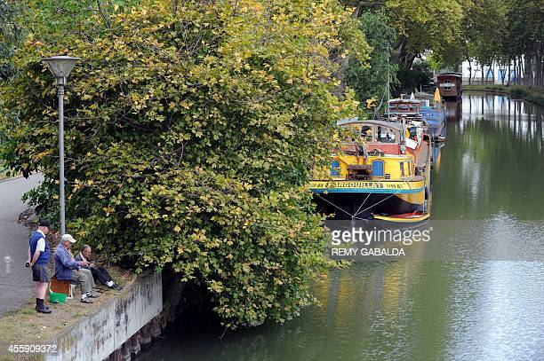 Persons fish with their rods on August 27 next to barges on the banks of the Canal du Midi in Toulouse southwestern France AFP PHOTO REMY GABALDA