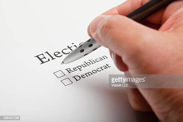 Persons hand completing election ballot slip