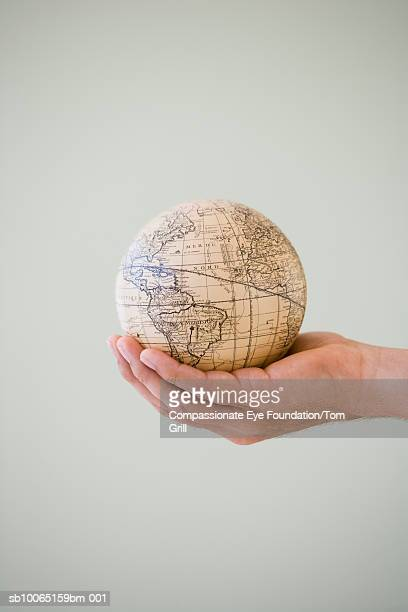 Person's hand holding globe