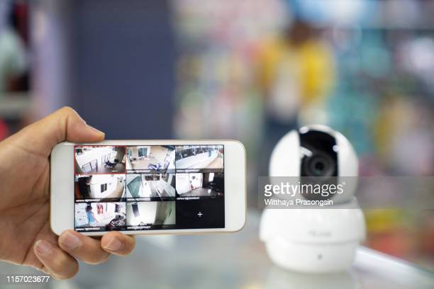 a person's hand holding mobile phone with cctv camera footage on screen - business security camera stock pictures, royalty-free photos & images