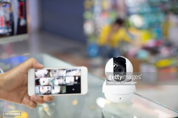 a person's hand holding mobile phone with cctv camera footage on screen - bewaken stockfoto's en -beelden