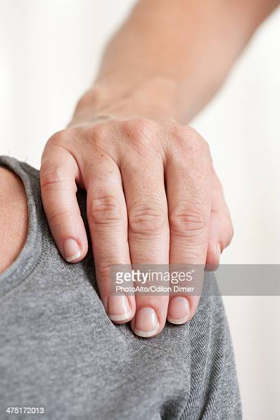 person's hand on another's shoulder - hand on shoulder stock pictures, royalty-free photos & images