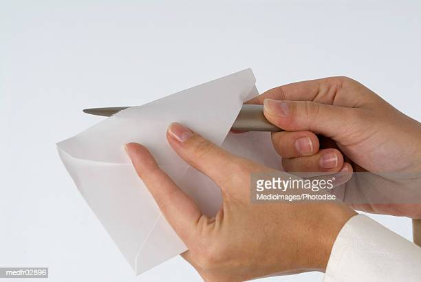 Person's hand opening letter with letter opener