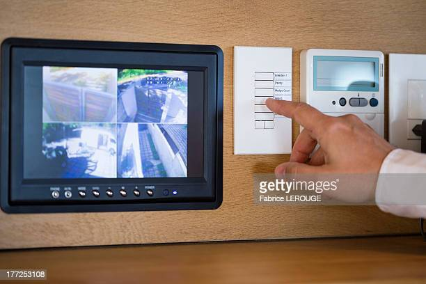 Person's hand pushing buttons for a security surveillance system at home