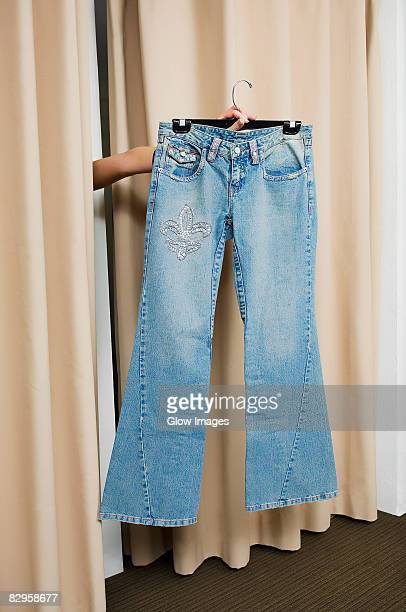 Person's hand showing a jeans through curtains