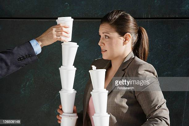 Person's hand stacking takeout coffees on woman's hands
