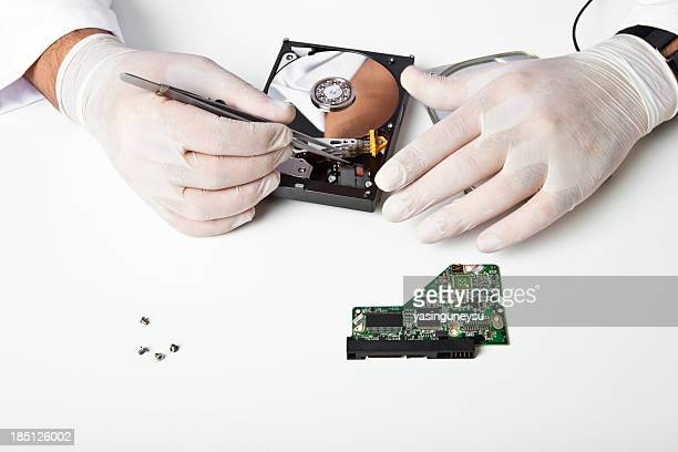 Person's hands in gloves working on a hard disk drive