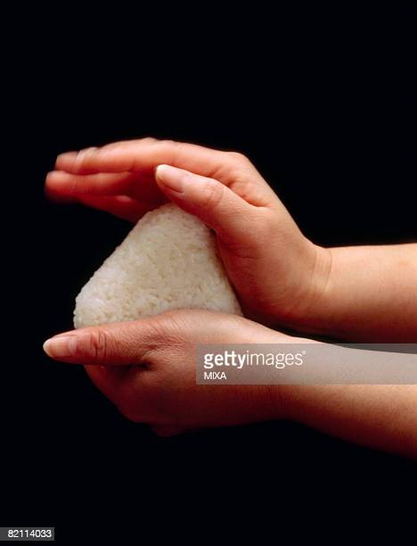 Person's hands making rice ball