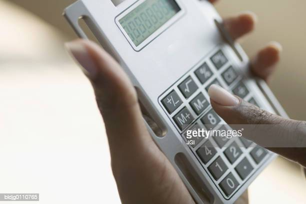 Person's hands operating a calculator