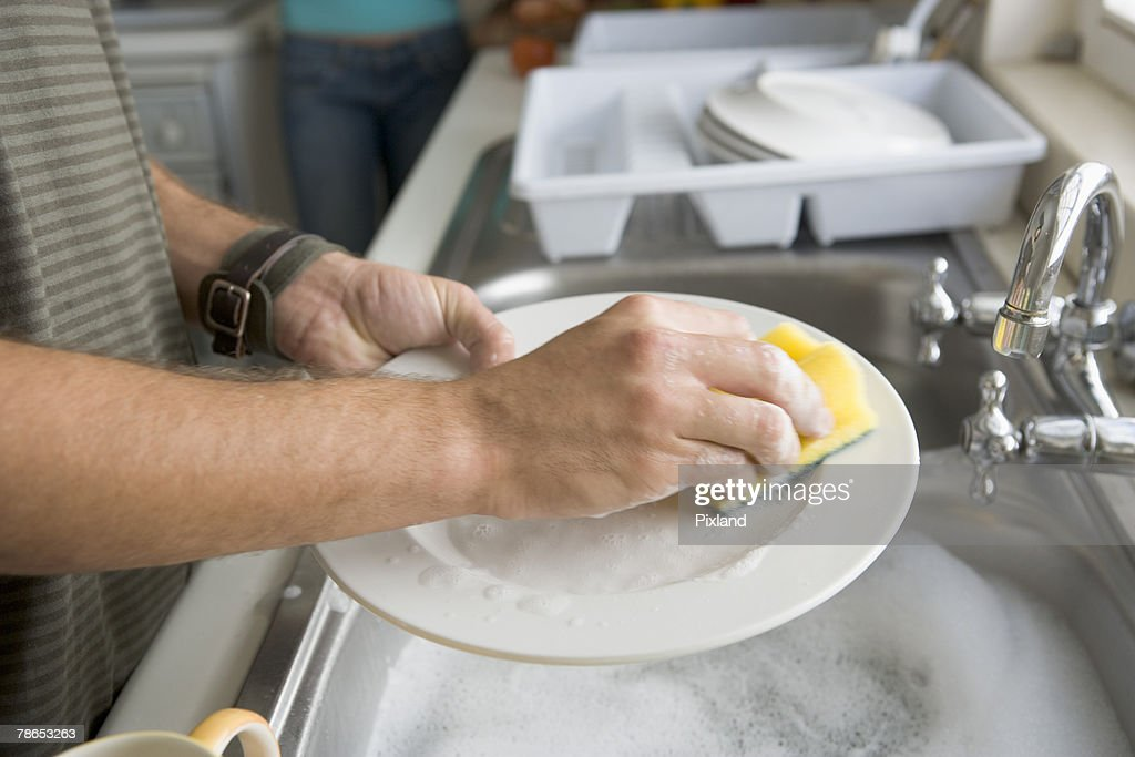 Person's hands washing dishes : Stock Photo