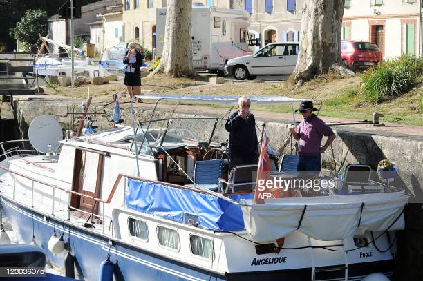 Persons have a coffee break on a pleasure boat on August 27 at the Gardouch lock in the Lauragais area on the banks of the Canal du Midi in Toulouse...