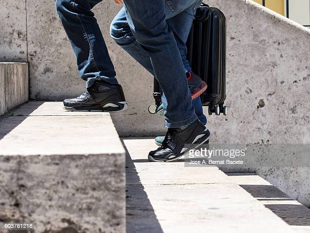 Persons' legs travelling, raising and lowering stairs with suitcases hotfoot in the city