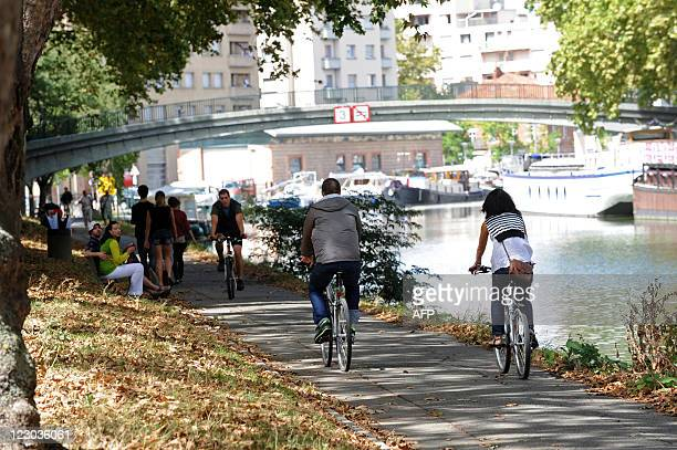 Persons ride bicycles among other people walking or sitting on August 27 on the banks of the Canal du Midi in Toulouse southwestern France AFP PHOTO...