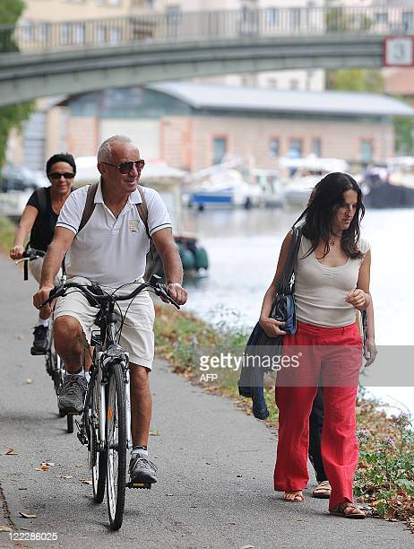 Persons ride cycles nex to pedestrians on August 27 on the banks of the Canal du Midi at the district of SaintSauveur in Toulouse southwestern France...