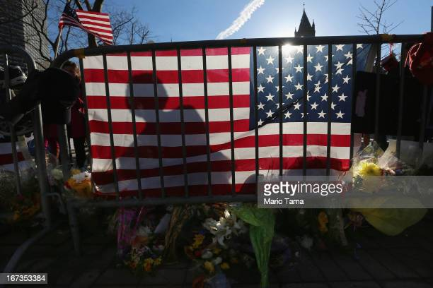 A person's shadow is cast on an American flag at a makeshift memorial in Copley Square near the site of one of the Boston Marathon bombings on April...