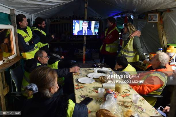 Persons wearing yellow vests watch TV under a tent in Montabon near Le Mans on December 10 2018 as French president delivers a tv speech following...