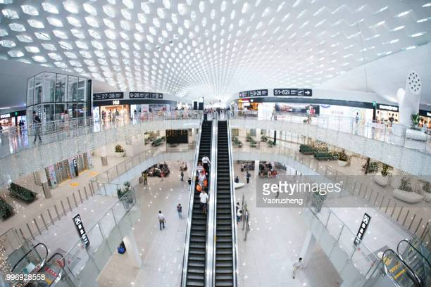perspective escalator stairway inside modern building,shenzhen airport,china - shopping mall stock pictures, royalty-free photos & images