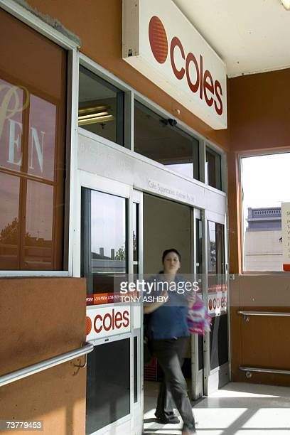 A shopper walks out of a Coles supermarket in Perth 03 April 2007 Conglomerate Wesfarmers said 03 April it had led a share raid on Australian retail...