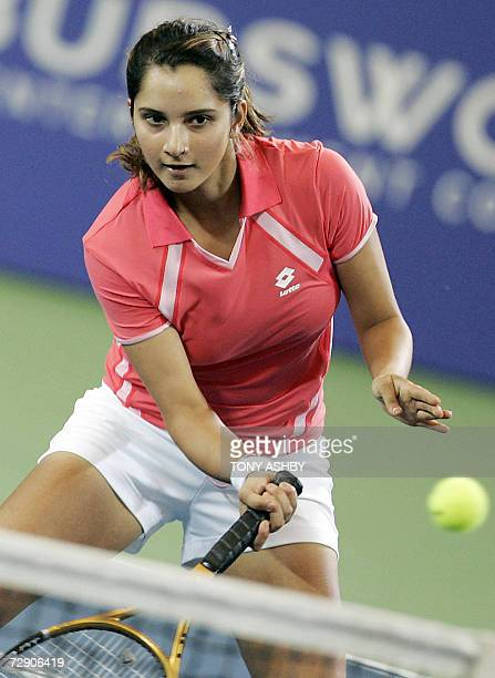 Sania Mirza of India returns a shot over the net as she and partner Rohan Bopanna go on to win their doubles match against Czech Republic players...