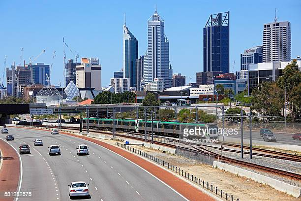 Perth cityscape with electric train running down freeway.