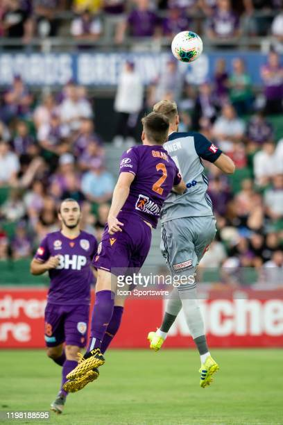Perth Glory Defender Alex Grant and Melbourne Victory Forward Nils Ola Toivonen go for the ball during the round 17 A-League soccer match between...