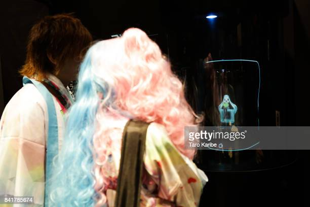 Pertisipants looking at Hologram virtual home robot 'Living With Hatsune Miku' developed by Gatebox displayed during the 'Magical Mirai 2017' at...