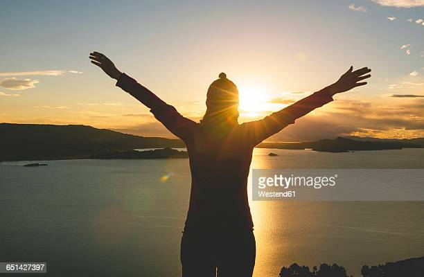Peru, Amantani Island, silhouette of woman with raised arms enjoying sunset from Pachamama peak