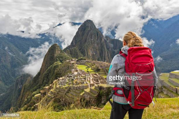 Peru, Andes, Urubamba Valley, tourist with red backpack at Machu Picchu with mountain Huayna Picchu