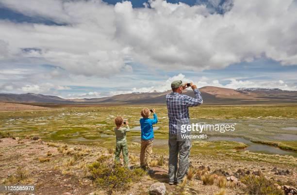 peru, chivay, colca canyon, father and sons taking pictures of swamp landscape in the andes - paisajes de peru fotografías e imágenes de stock