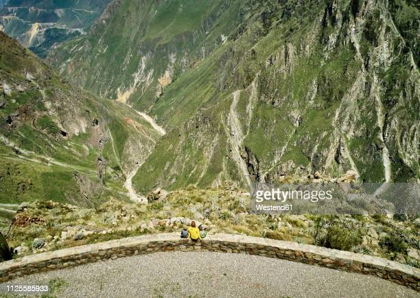 peru, chivay, colca canyon, woman sitting with sons on wall looking at canyon - paisajes de peru fotografías e imágenes de stock