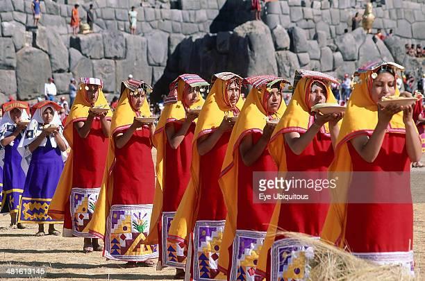 Peru Cusco Department Sacsayhuaman Parade of women offering food at Inti Raymi Inca walls behind