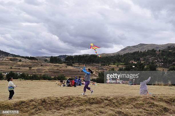 Peru Cusco Kinder spielen auf einem Hochplateau mit ihren Drachen