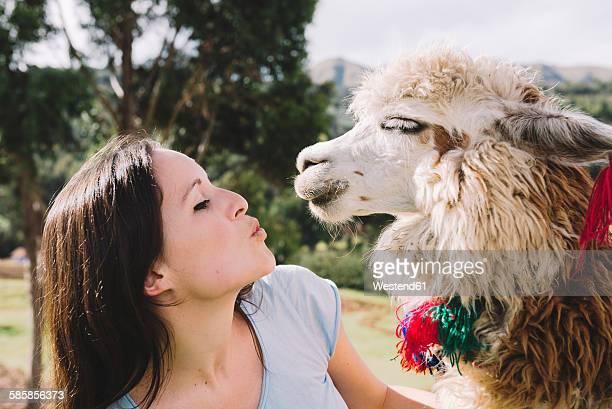 Peru, Cusco, young woman face to face to an alpaca