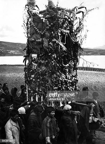 Peru Indios Feste/Rituale 'Dia del Compadre' im Altiplano Ein Prozessionszug auf dem Weg zu einem KultplatzDer Männer tragen das mit Früchten und...