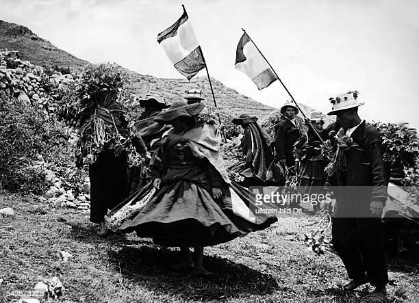 Peru Indios Feste/Rituale 'Dia del Compadre' Zeremonie im Hochland Frauen drehen sich im Tanz Männer mit Fahnen sowie Korn und Feldfrüchten auf...