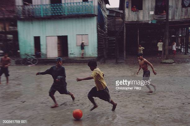 Peru, Iquitos, boys (8-9) playing football in muddy street