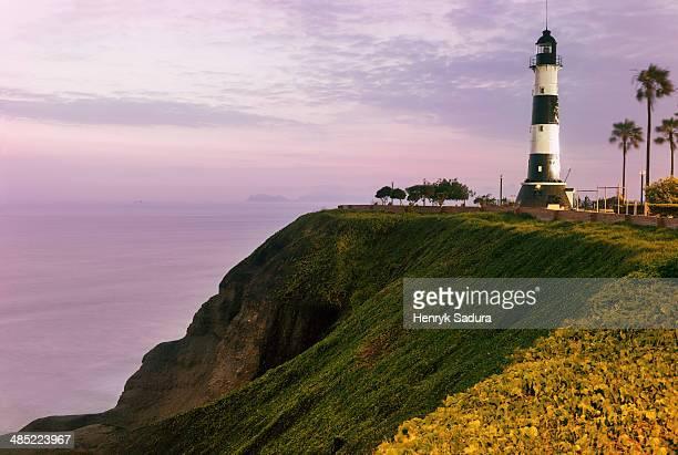 peru, lima, miraflores, lighthouse at sunset - lima peru stock photos and pictures