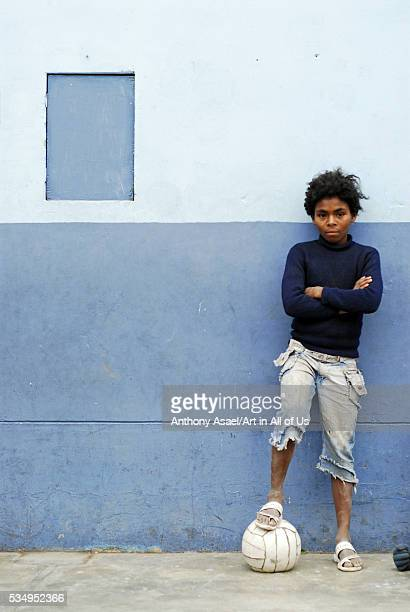 Peru Lima portrait of a serious peruvian African boy with arms crossed and one leg over a ball
