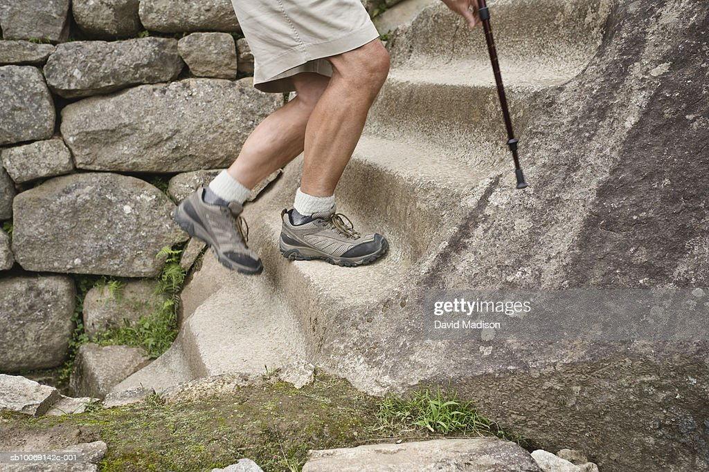 Peru, Machu Picchu, man climbing stone steps, low section : Stockfoto
