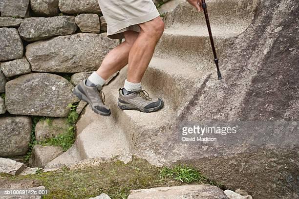 Peru, Machu Picchu, man climbing stone steps, low section